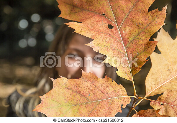 Young woman plays with branches with autumn leaves - csp31500812