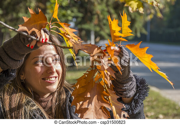 Young woman plays with branches with autumn leaves - csp31500823