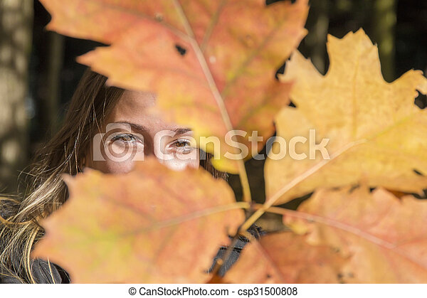 Young woman plays with branches with autumn leaves - csp31500808