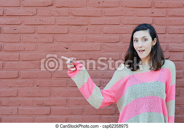 Young woman pointing at copy space - csp62358975