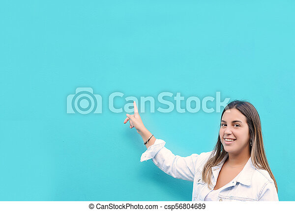 Young woman pointing at copy space - csp56804689