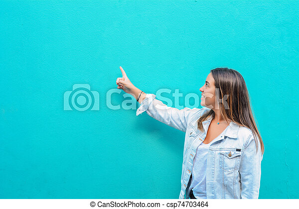 Young woman pointing at copy space - csp74703464