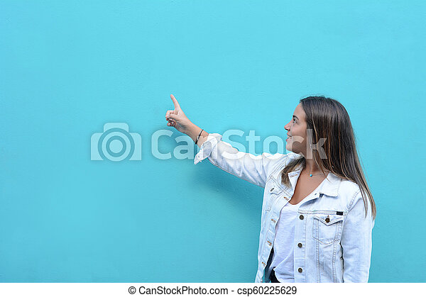 Young woman pointing at copy space - csp60225629