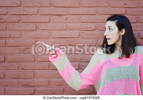 Young woman pointing at copy space - csp61974528