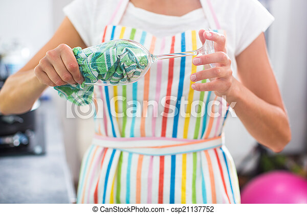 Young woman polishing a glass in her modern kitchen - csp21137752