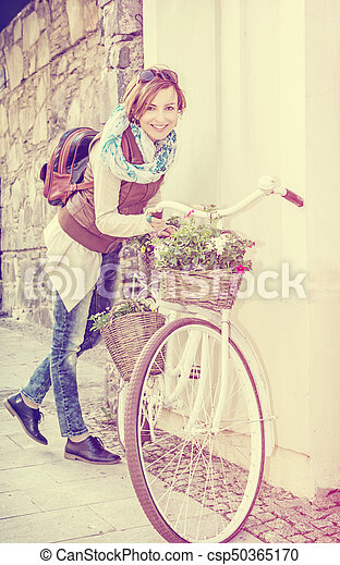 Young woman posing with retro bicycle with wicker baskets, beauty photo filter - csp50365170