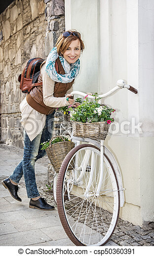 Young woman posing with retro bicycle with wicker garden baskets - csp50360391