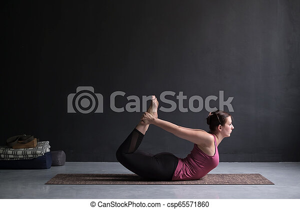 young woman practicing yoga bow pose dhanurasana side view