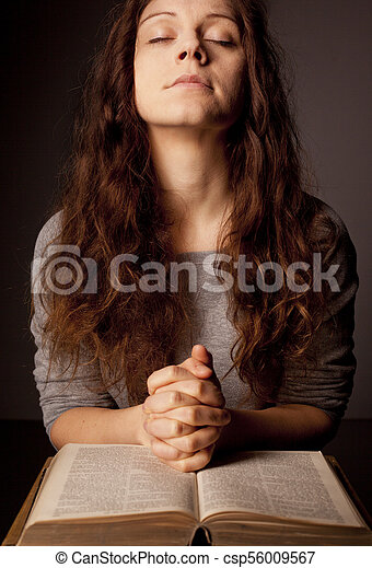 Young woman praying on holy bible with rosary - csp56009567