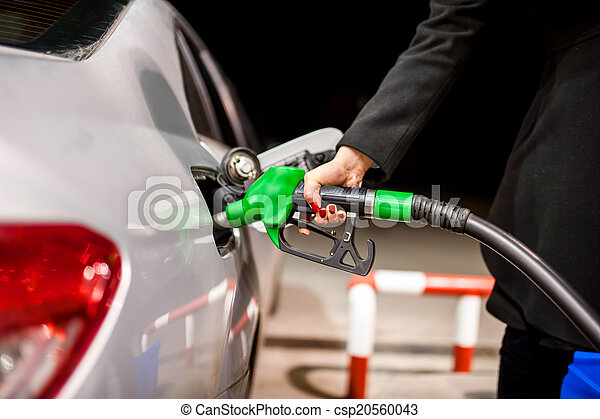 Young woman pumping gas in car at petrol station - csp20560043