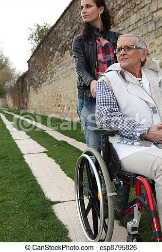 Young woman pushing an elderly lady in a wheelchair - csp8795826
