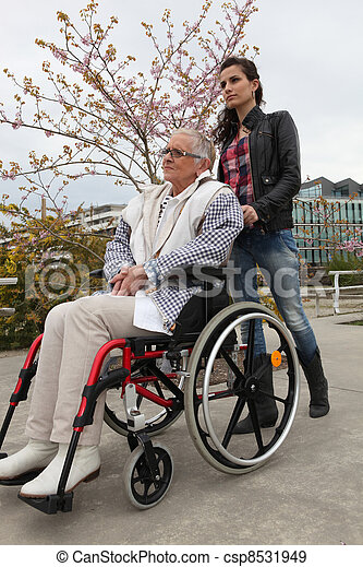 Young woman pushing an elderly lady in a wheelchair - csp8531949