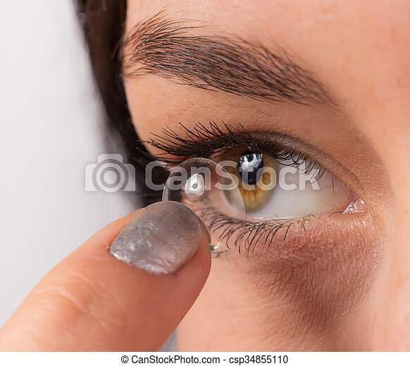 Young woman putting contact lens in her eye. - csp34855110