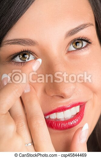 Young woman putting contact lens in her eye. - csp45844469