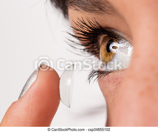 Young woman putting contact lens in her eye. - csp34855102