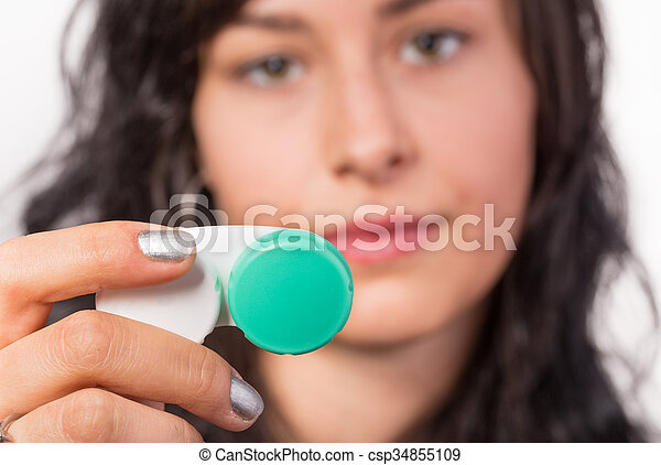 Young woman putting contact lens in her eye. - csp34855109