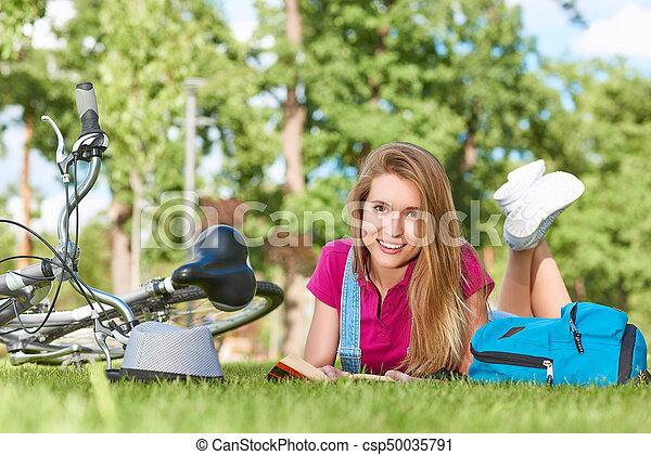 Young happy beautiful woman smiling to the camera lying on the grass at the park enjoying reading a book after cycling active lifestyle student recreation hobby leisure living positivity hipster.