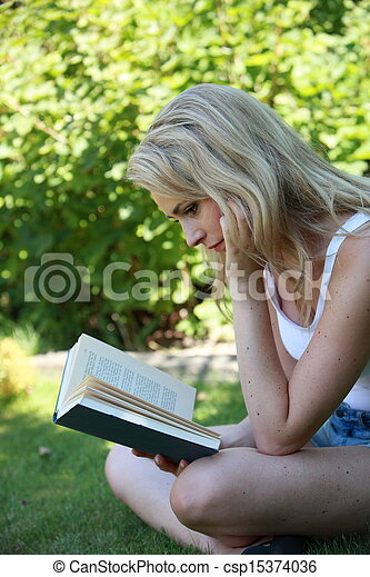 Young woman reading a book in the garden - csp15374036
