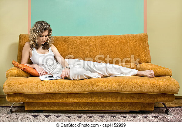 Young woman reading book on sofa - csp4152939