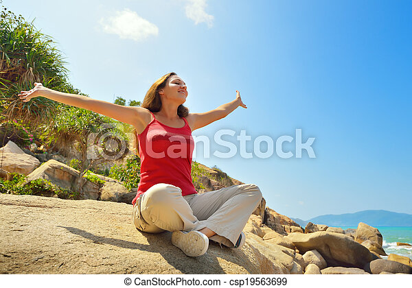 Young woman resting sitting on edge of a cliff. - csp19563699