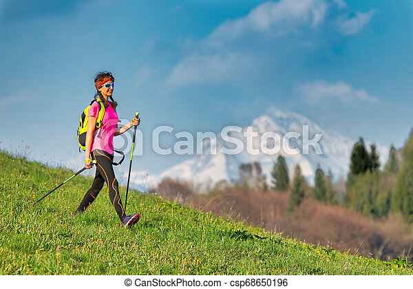 Young woman returning from a Nordic walking excursion in the mountains in spring - csp68650196