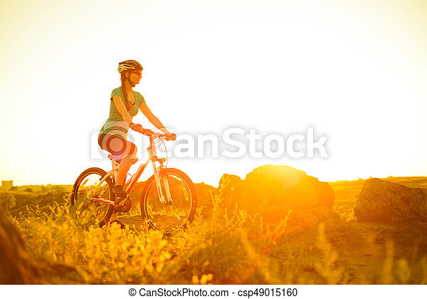 Young Woman Riding Mountain Bike on the Summer Rocky Trail at Beautiful Sunset. Travel, Sports and Adventure Concept. - csp49015160