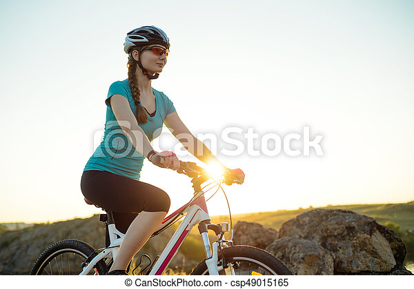 Young Woman Riding Mountain Bike on the Summer Rocky Trail at Beautiful Sunset. Travel, Sports and Adventure Concept. - csp49015165