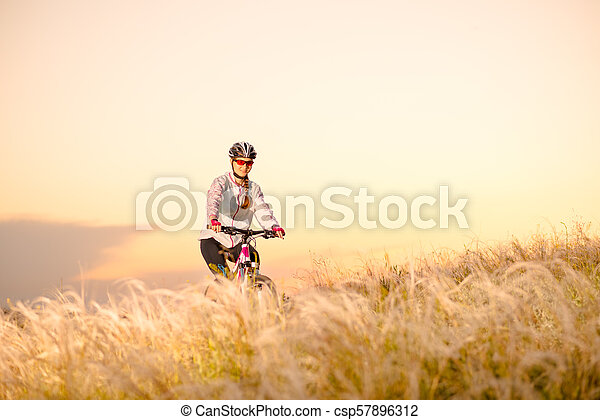 Young Woman Riding Mountain Bikes in the Beautiful Field of Feather Grass at Sunset. Adventure and Travel. - csp57896312