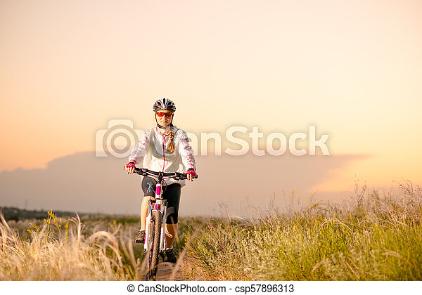 Young Woman Riding Mountain Bikes in the Beautiful Field of Feather Grass at Sunset. Adventure and Travel. - csp57896313