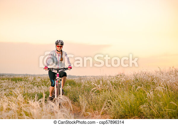 Young Woman Riding Mountain Bikes in the Beautiful Field of Feather Grass at Sunset. Adventure and Travel. - csp57896314