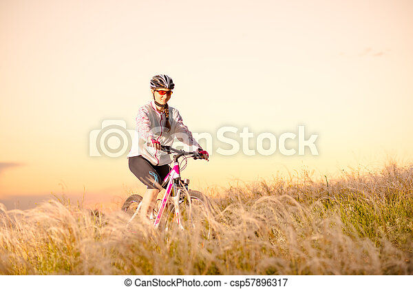 Young Woman Riding Mountain Bikes in the Beautiful Field of Feather Grass at Sunset. Adventure and Travel. - csp57896317