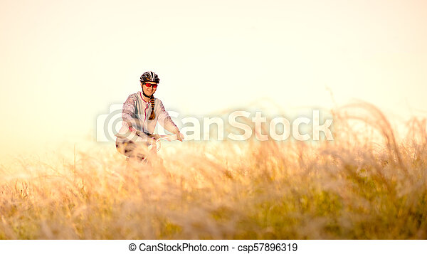 Young Woman Riding Mountain Bikes in the Beautiful Field of Feather Grass at Sunset. Adventure and Travel. - csp57896319