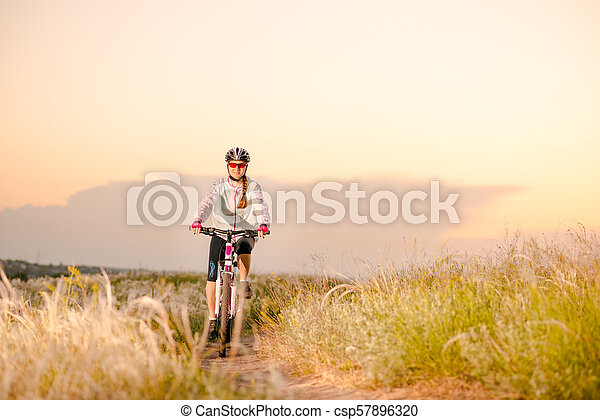 Young Woman Riding Mountain Bikes in the Beautiful Field of Feather Grass at Sunset. Adventure and Travel. - csp57896320