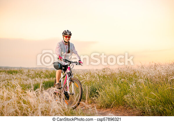 Young Woman Riding Mountain Bikes in the Beautiful Field of Feather Grass at Sunset. Adventure and Travel. - csp57896321