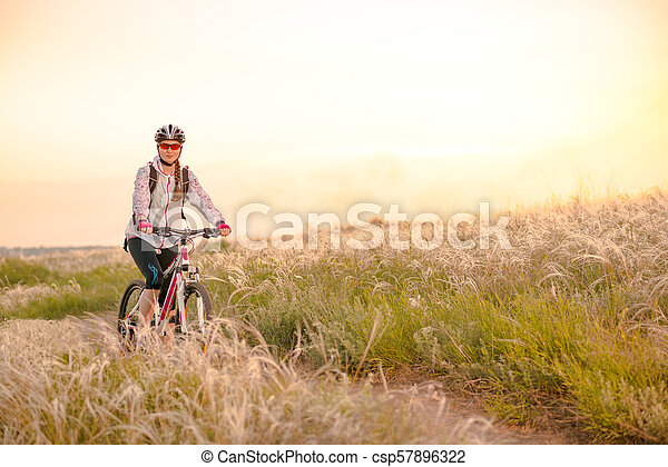 Young Woman Riding Mountain Bikes in the Beautiful Field of Feather Grass at Sunset. Adventure and Travel. - csp57896322