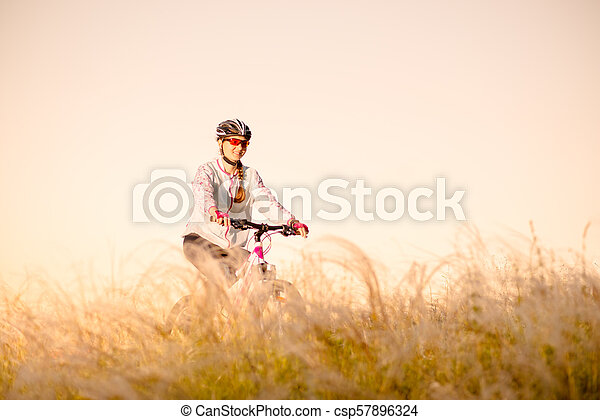 Young Woman Riding Mountain Bikes in the Beautiful Field of Feather Grass at Sunset. Adventure and Travel. - csp57896324