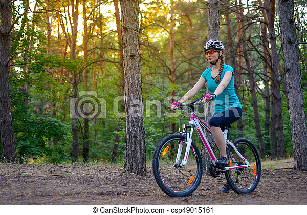 Young Woman Riding the Bike on the Trail in Beautiful Fairy Pine Forest. Adventure and Travel Concept. - csp49015161