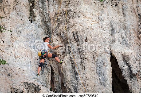 Young woman rock climbing on white mountain - csp50729510