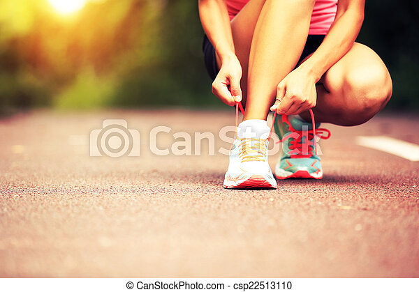 young woman runner tying shoelaces - csp22513110