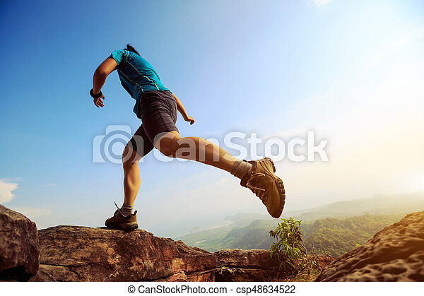 Young woman running and jumping on mountain peak - csp48634522