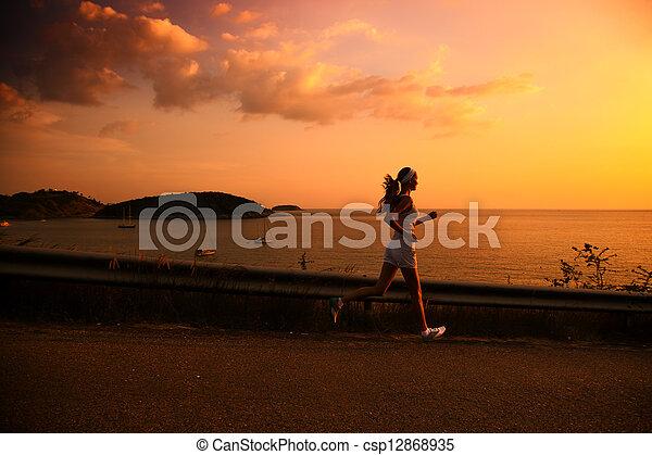 Young woman running at sunset - csp12868935