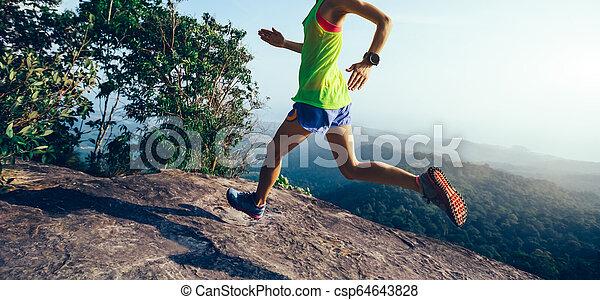 Young woman running on mountain peak cliff edge - csp64643828