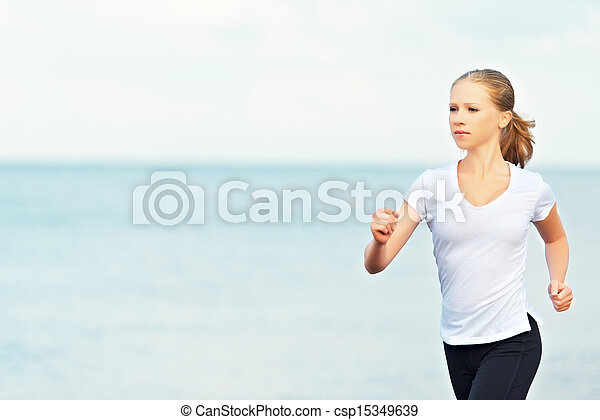young woman running on the beach on the coast of the Sea - csp15349639