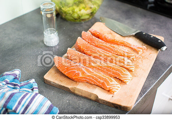 Young woman seasoning a salmon filet in her modern kitchen - csp33899953