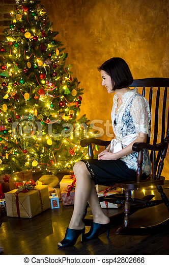 Fantastic Young Woman Sits In A Rocking Chair Near Christmas Tree Machost Co Dining Chair Design Ideas Machostcouk