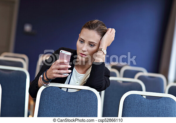 Young woman sitting alone in conference room - csp52866110