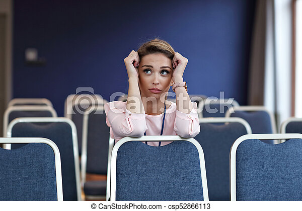 Young woman sitting alone in conference room - csp52866113