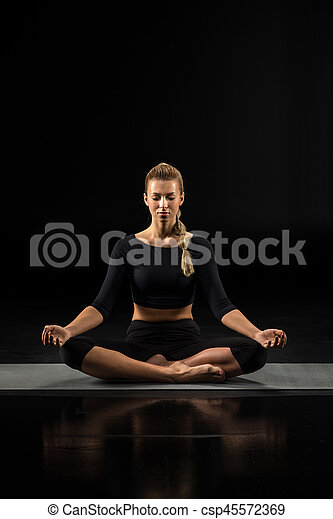 Young woman sitting and meditating - csp45572369
