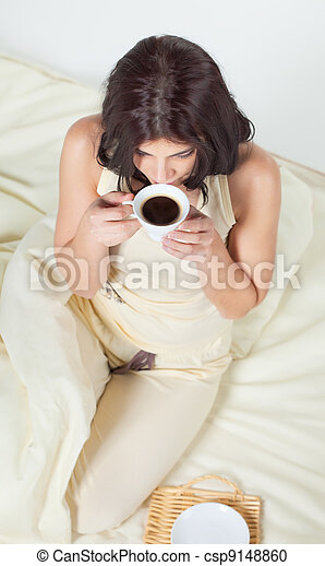 Young woman sitting in bed drinking coffee - csp9148860