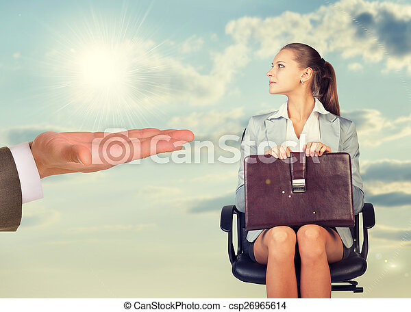 Young woman sitting in chair and looking at mans hand - csp26965614